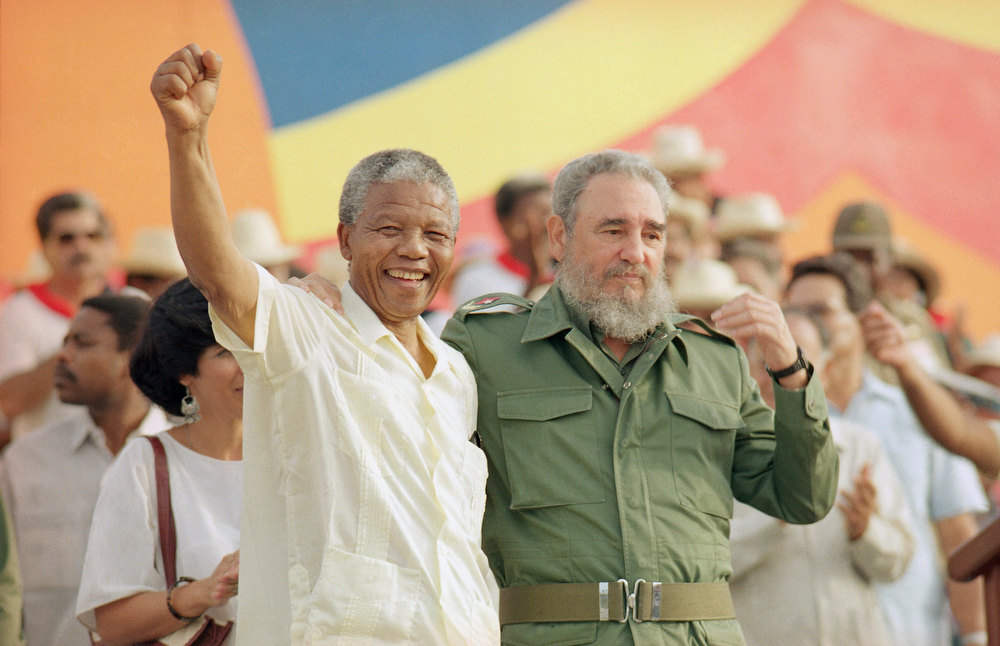Description of . In this July 27, 1991 file photo, Cuban President Fidel Castro, right, and African leader Nelson Mandela gesture during the celebration of the