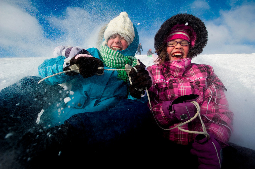 . Emily Dresbach, left, 12, and Kelsey Blum, 11, sled down the hill on Thursday, Dec. 20, 2012 at Holmes Lake in Lincoln, Neb. (AP Photo/The Journal-Star, Adam Wolffbrandt) LOCAL TV OUT; KOLN-TV OUT; KGIN-TV OUT; KLKN-TV OUT