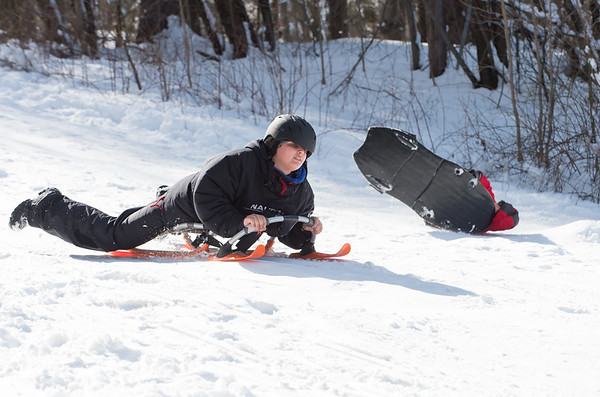 03/04/19 Wesley Bunnell | Staff Noah Botto, age 12, sleds his way down a hill at Page Park on Monday afternoon as a fellow sledder wipes out after going over a small ramp behind him.