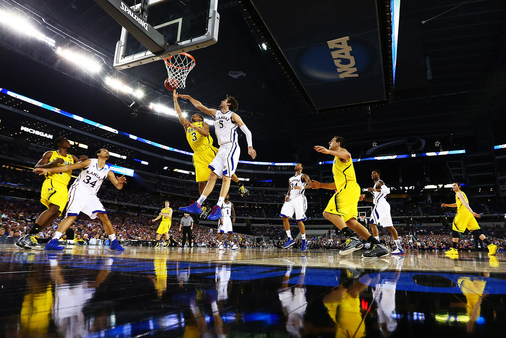 . ARLINGTON, TX - MARCH 29:  Jeff Withey #5 of the Kansas Jayhawks blocks a shot by Trey Burke #3 of the Michigan Wolverines in the second half during the South Regional Semifinal round of the 2013 NCAA Men\'s Basketball Tournament at Dallas Cowboys Stadium on March 29, 2013 in Arlington, Texas.  (Photo by Tom Pennington/Getty Images)