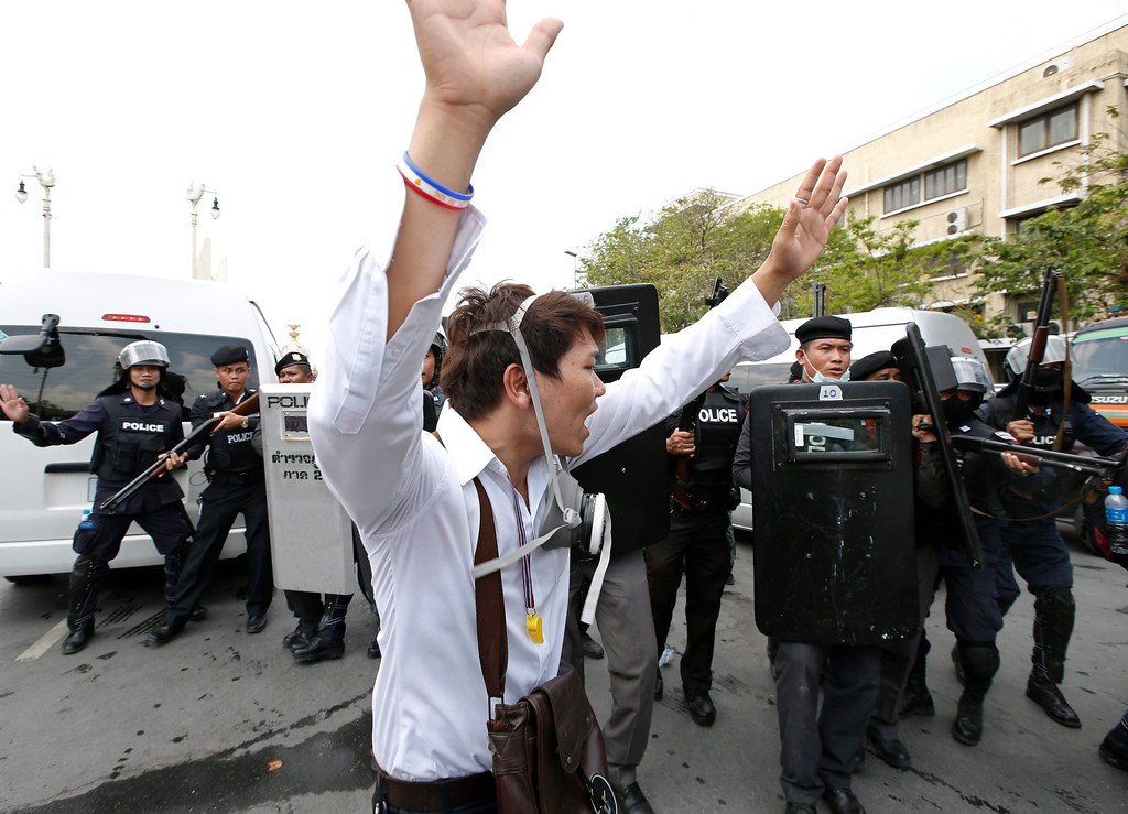 . A Thai anti-government protester rises his hands up as he faces with a unit of riot police officers during clashes at a protest site in Bangkok, Thailand, 18 February 2014. EPA/RUNGROJ YONGRIT