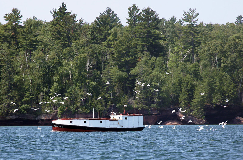 An enclosed fishing boat, swarmed with gulls.