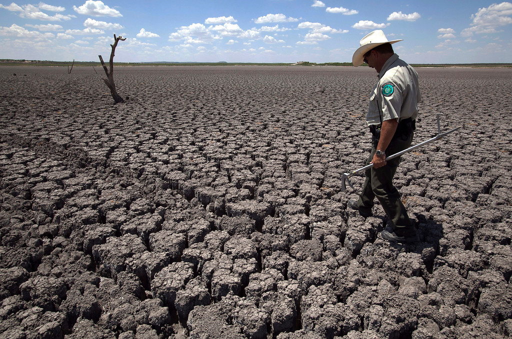 . In this Aug. 3, 2011 file photo, Texas State Park police officer Thomas Bigham walks across the cracked lake bed of O.C. Fisher Lake in San Angelo, Texas.  (AP Photo/Tony Gutierrez)