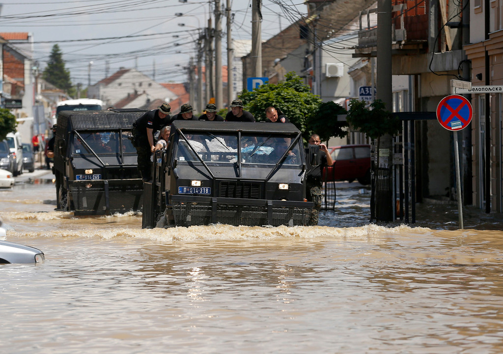 . A police vehicle drives through flooded street in Obrenovac, some 30 kilometers (18 miles) southwest of Belgrade, Serbia, Tuesday, May 20, 2014. Serbia, Bosnia and Croatia have been hit by the worst flooding in more than 100 years, forcing half a million people out of their homes and leading to more than three dozen deaths. (AP Photo/Darko Vojinovic)
