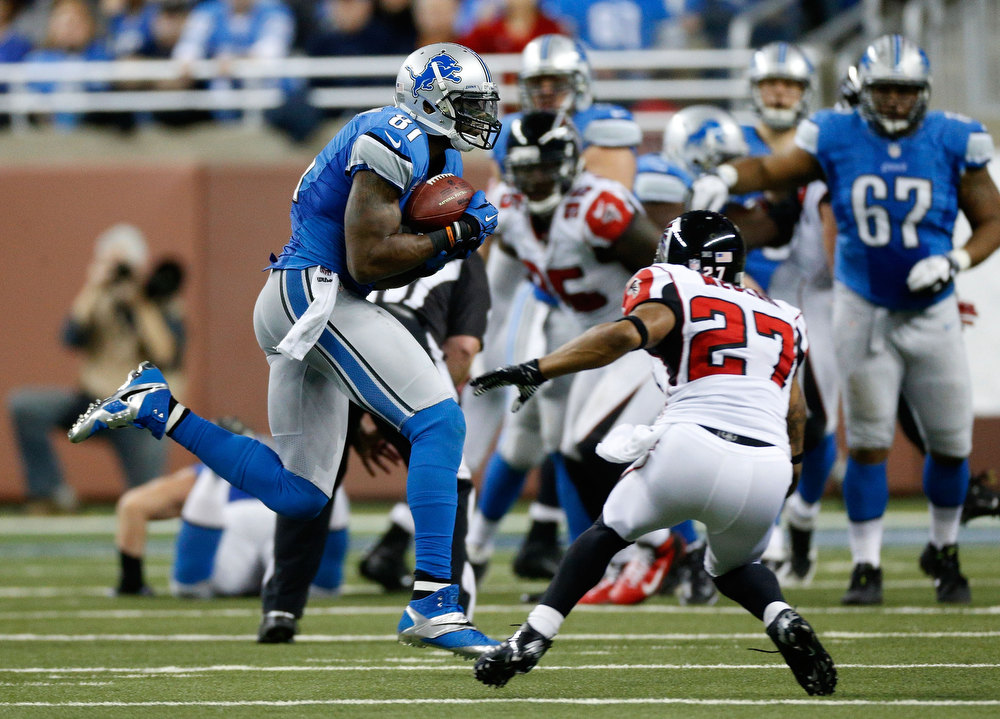 . Calvin Johnson #81 of the Detroit Lions catches a fourth quarter 26-yard pass in front of Robert McClain #27 of the Atlanta Falcons at Ford Field on December 22, 2012 in Detroit, Michigan.  Johnson broke the NFL single season yardage record formally held by Jerry Rice during this play. (Photo by Gregory Shamus/Getty Images)