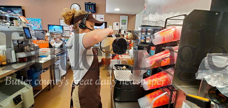 Emily Andre, a Dunkin' crew member, crafts a whip cream topped coffee drink on Monday at the Butler location. Photo by Nathan Bottiger