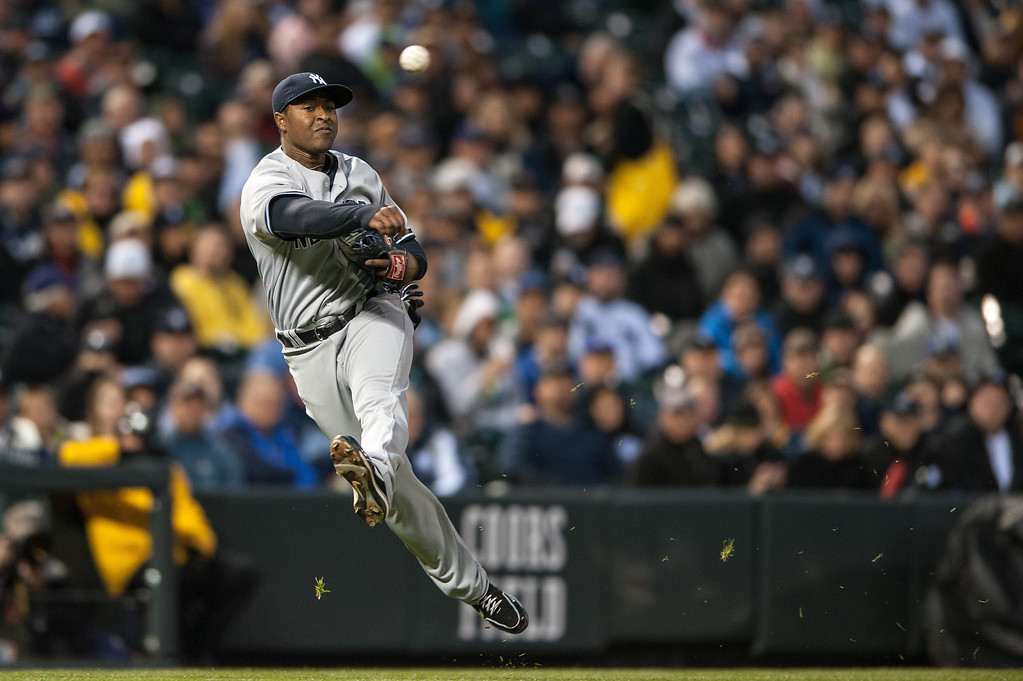 . Chris Nelson #39 of the New York Yankees makes an acrobatic throw from third base to put out a runner at first base in the fourth inning of a game against the Colorado Rockies at Coors Field on May 8, 2013 in Denver, Colorado.  (Photo by Dustin Bradford/Getty Images)