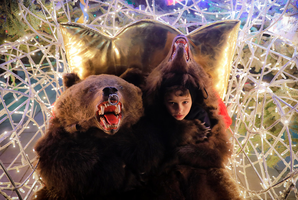 . In this Thursday, Dec. 28, 2017, picture children wearing bear fur costumes pose at a Christmas fair, in Piatra Neamt, Romania. Hundreds of people descend on the sleepy northern Romanian city of Comanesti every year dressed head to toe like bears, in costumes made from real fur, with the heads attached. It\'s a tradition that originated in pre-Christian times, when dancers wearing colored costumes or animal furs went from house to house in villages, singing and dancing to ward off evil. (AP Photo/Vadim Ghirda)