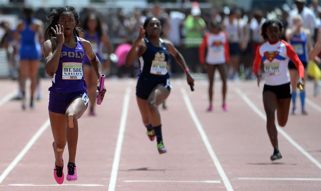 . Long Beach Poly\'s Ariana Washington, left, runs final leg of the 4x100 meter relay Invitational during the Mt. SAC Relays in Hilmer Lodge Stadium on the campus of Mt. San Antonio College in Walnut, Calif., on Saturday, April 19, 2014.  (Keith Birmingham Pasadena Star-News)