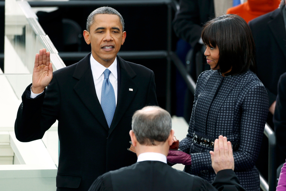. U.S. President Barack Obama (L) is sworn in by Supreme Court Justice John Roberts, as first lady Michelle Obama looks on during inauguration ceremonies in Washington, January 21, 2013. REUTERS/Kevin Lamarque