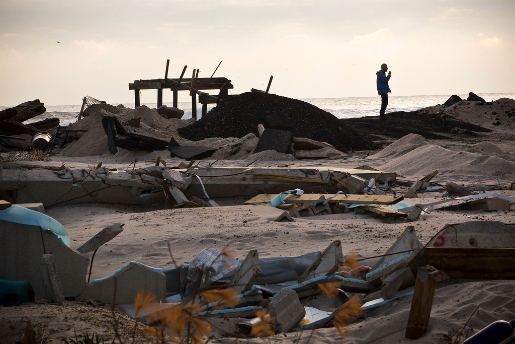. A man smokes a cigarette while surveying the damage caused by Hurricane Sandy, in the Ortley Beach area of Toms River, New Jersey November 28, 2012. The storm made landfall along the New Jersey coastline on October 29. REUTERS/Andrew Burton