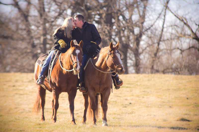 Romantic Couple horseback riding at Perks Ranch during winter engagement photos in Rockford, IL