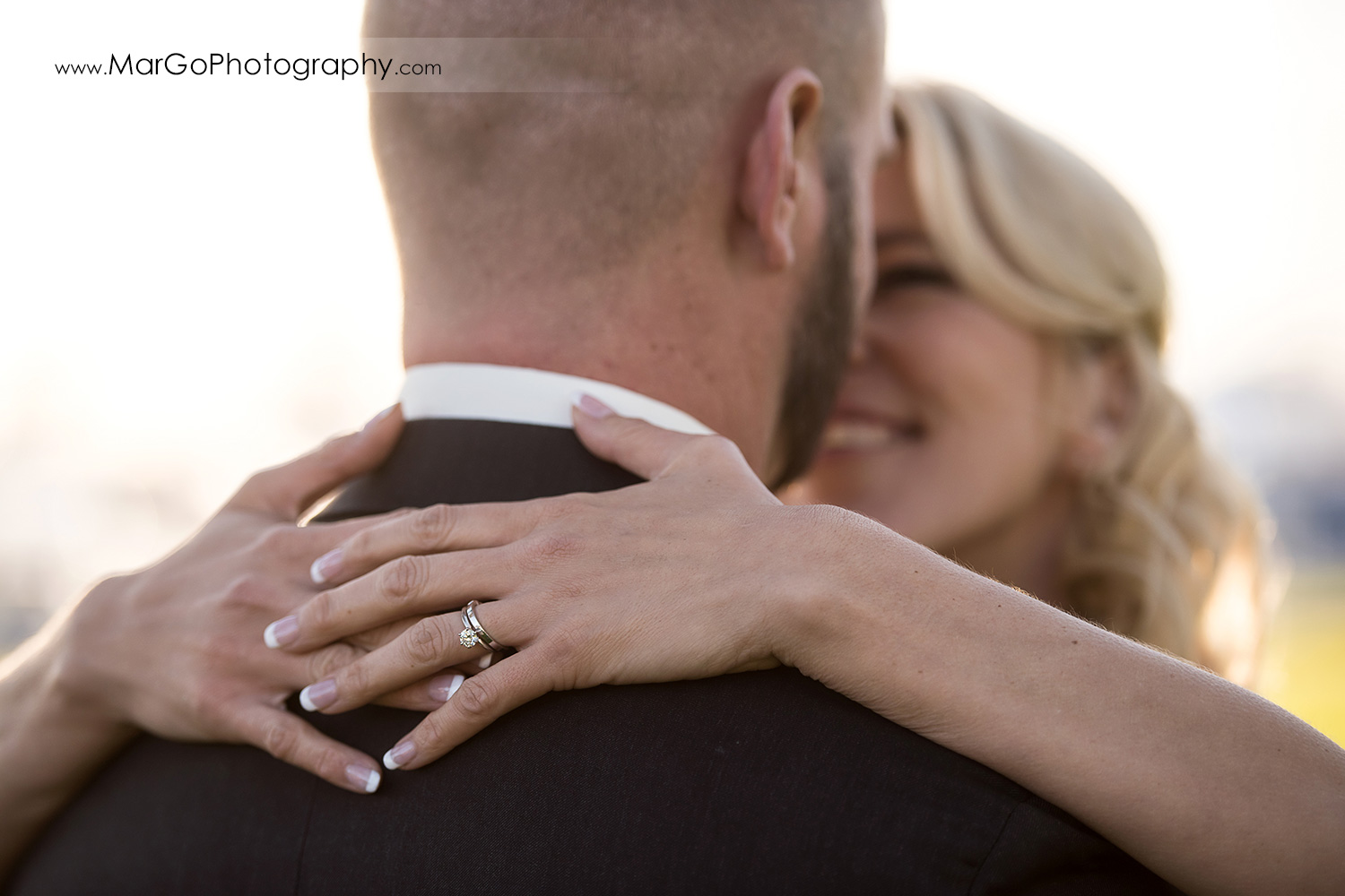 bride holding hands on groom's neck and showing wedding rings at San Diego Marina Village