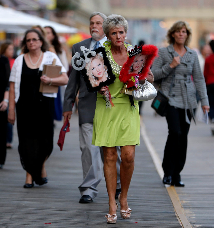 . Mary Walker holds photographs of Miss Georgia Maggie Bridges before the Miss America 2015 pageant, Sunday, Sept. 14, 2014, in Atlantic City, N.J. (AP Photo/Julio Cortez)