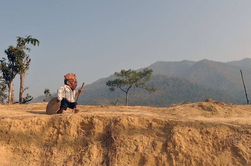 . Chandra Bahadur Dangi, a 72-year-old Nepali who claims to be the world\'s shortest man at 56 centimetres (22 inches) in height, walk near his home in Reemkholi village in Dang district, some 540 kilometres southwest of Kathmandu on February 21, 2012. Dangi will embark to the capital city as Guinness World Records experts are due to arrive in Nepal to measure a 72-year-old claiming to be the world\'s shortest man. AFP PHOTO/Prakash  MATHEMA/AFP/Getty Images
