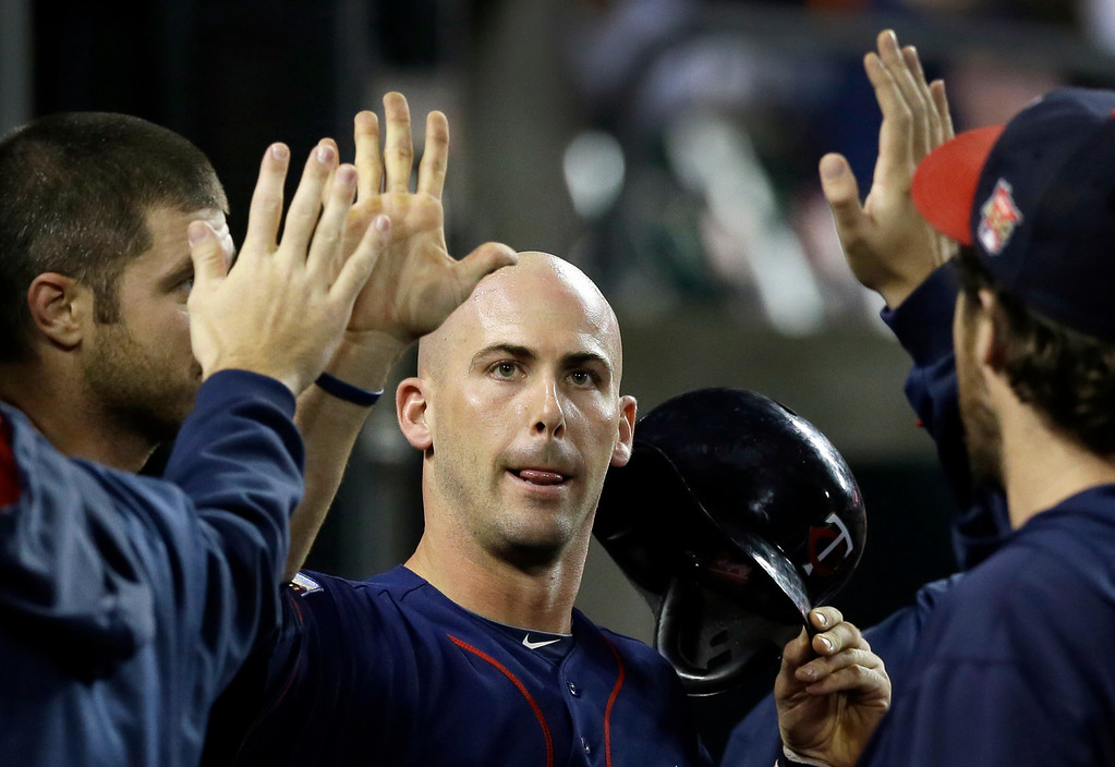 . Minnesota Twins\' Eric Fryer is congratulated in the dugout after scoring on a single by teammate Chris Herrmann during the seventh inning of a baseball game against the Detroit Tigers in Detroit, Saturday, Sept. 27, 2014. (AP Photo/Carlos Osorio)