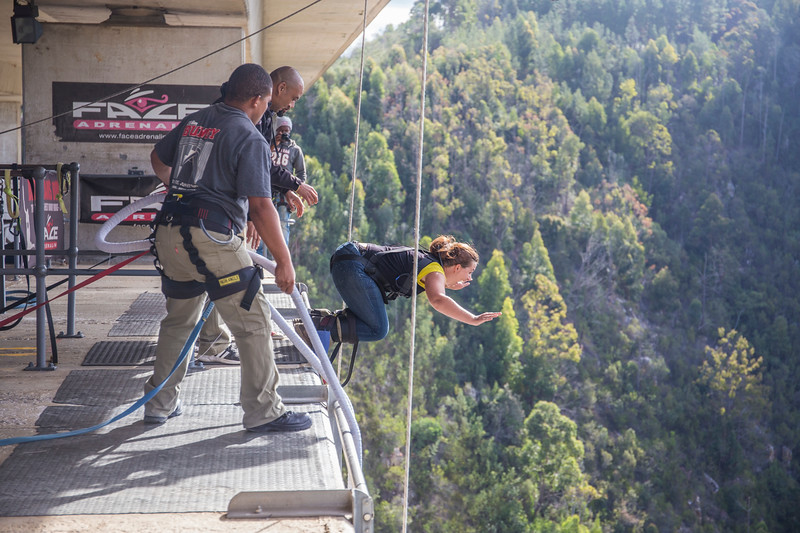 woman bungee jumping off of bridge