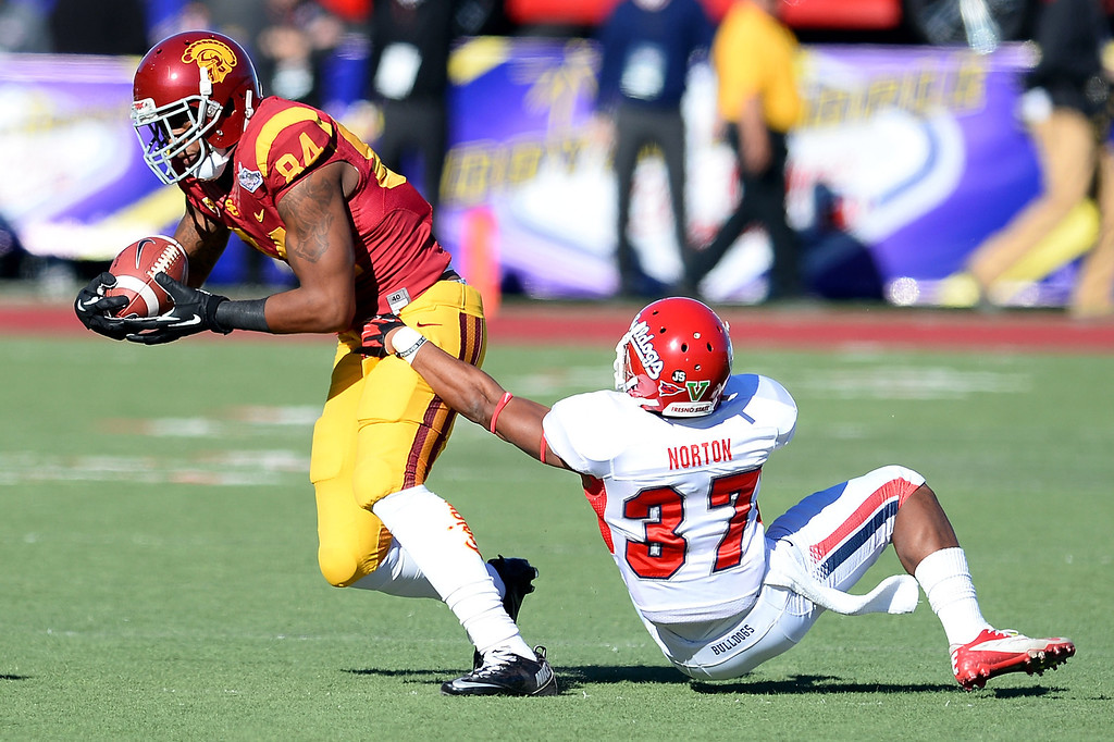 . LAS VEGAS, NV - DECEMBER 21:  Darreus Rogers #84 of the USC Trojans breaks a tackle by Jonathan Norton #37 of the Fresno State Bulldogs during the Royal Purple Las Vegas Bowl at Sam Boyd Stadium on December 21, 2013 in Las Vegas, Nevada.  (Photo by Ethan Miller/Getty Images)