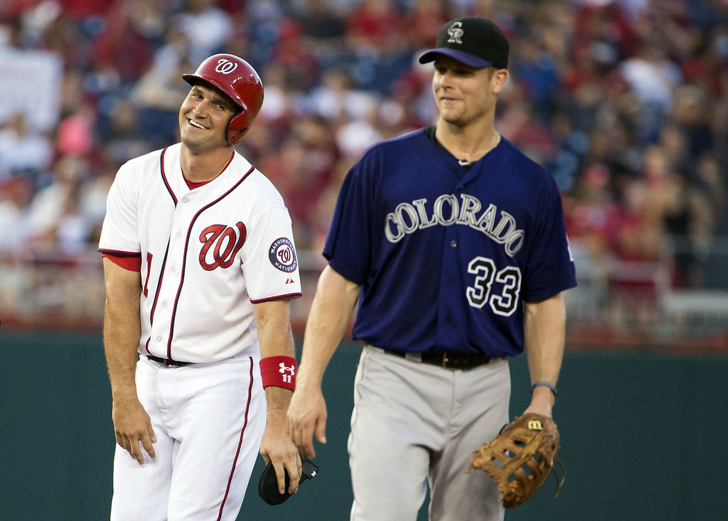 . Washington Nationals\' Ryan Zimmerman, left, stands near Colorado Rockies first baseman Justin Morneau after hitting a double during the fourth inning of a baseball game at Nationals Park, on Monday, June 30, 2014, in Washington. (AP Photo/ Evan Vucci)