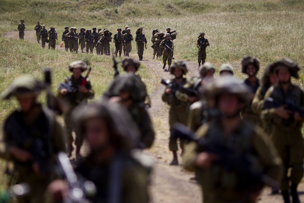 . Israeli soldiers march during a military exercise in the Israeli controlled Golan Heights, near the border with Syria, Tuesday, May 7, 2013. (AP Photo/Ariel Schalit)