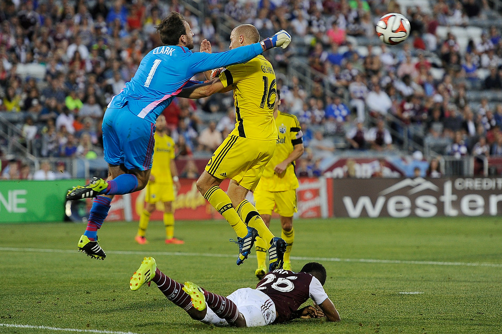 . Steve Clark #1 of the Columbus Crew and Eric Gehrig #16 of the Columbus Crew over Deshorn Brown #26 of the Colorado Rapids during an MLS match at Dick\'s Sporting Goods Park on July 4, 2014, in Commerce City, Colorado. Gehrig was injured on the play, but walked off the field under his own power. (Photo by Daniel Petty/The Denver Post)