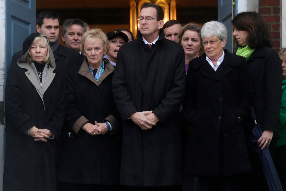 Description of . Connecticut Gov. Dan Malloy, center, stands with other officials to observe a moment of silence while bells ring 26 times in Newtown, Conn., Friday, Dec. 21, 2012, in honor of the 26 adults and children who were killed last Friday during the shooting at Sandy Hook Elementary School. (AP Photo/Seth Wenig)