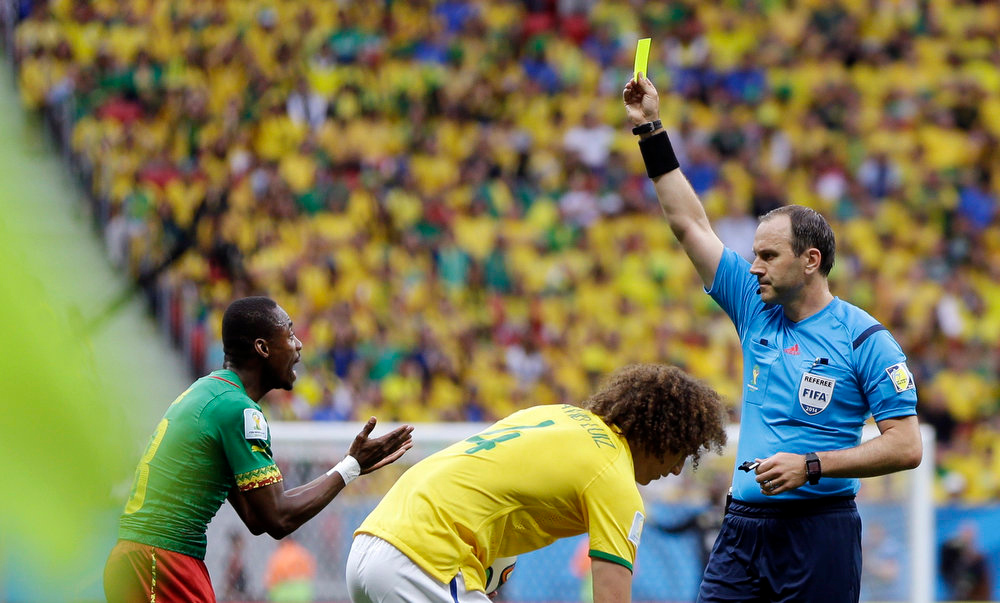 . Cameroon\'s Eyong Enoh, left, is booked by referee Jonas Eriksson from Sweden during the group A World Cup soccer match between Cameroon and Brazil at the Estadio Nacional in Brasilia, Brazil, Monday, June 23, 2014. (AP Photo/Andre Penner)