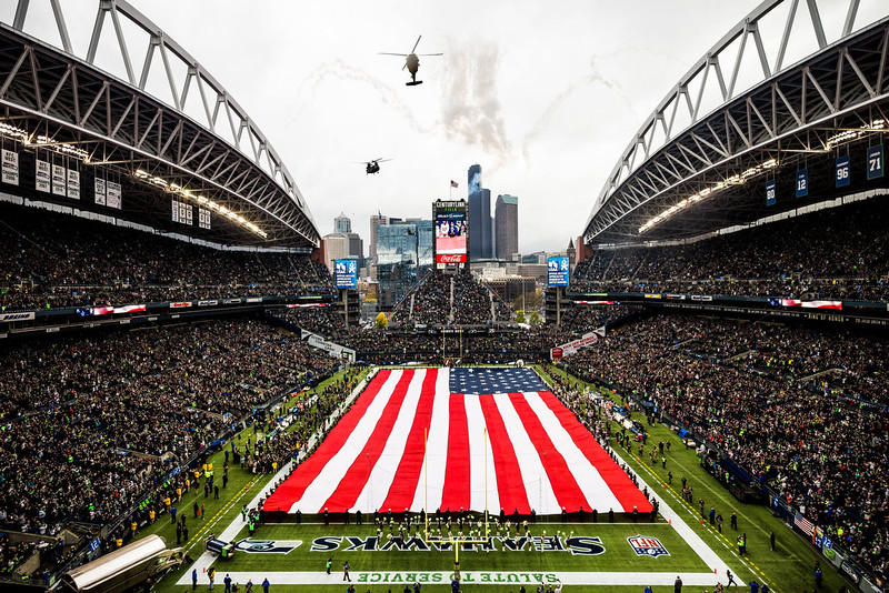 . Helicopters fly above the U.S flag-covered field before an NFL football game between the New York Giants and the Seattle Seahawks, Sunday, Nov. 9, 2014, in Seattle. (AP Photo/Seattlepi.com, Jordan Stead)