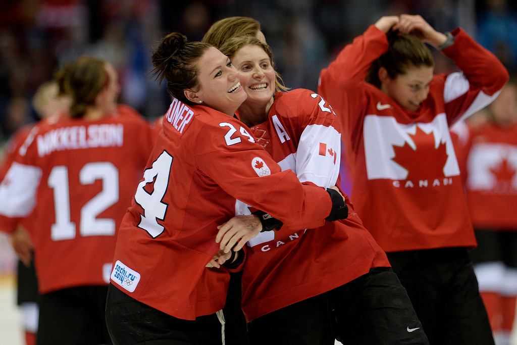 . SOCHI, RUSSIA - FEBRUARY 20: Natalie Spooner (24) of the Canada and Hayley Wickenheiser (22) hug after the overtime period of Canada\'s 3-2 gold medal ice hockey win over the U.S.A. Sochi 2014 Winter Olympics on Thursday, February 20, 2014 at Bolshoy Ice Arena. (Photo by AAron Ontiveroz/ The Denver Post)