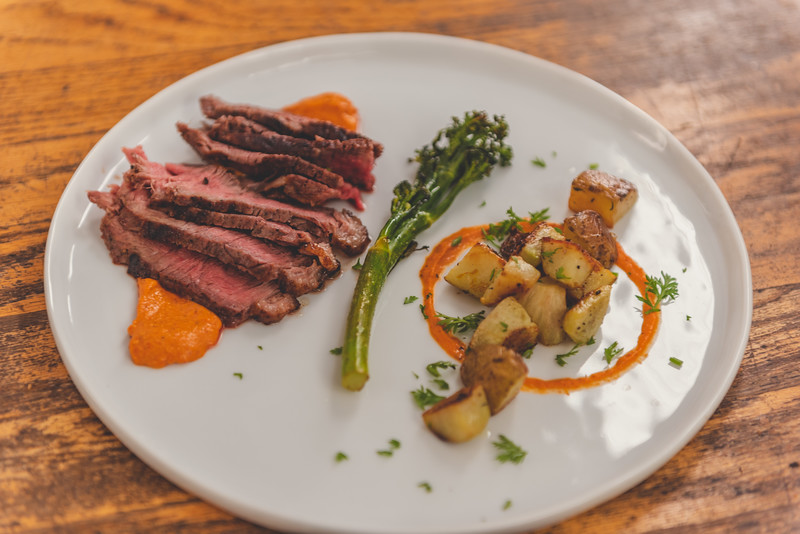 Steak with roast root vegetables, broccolini, and romesco