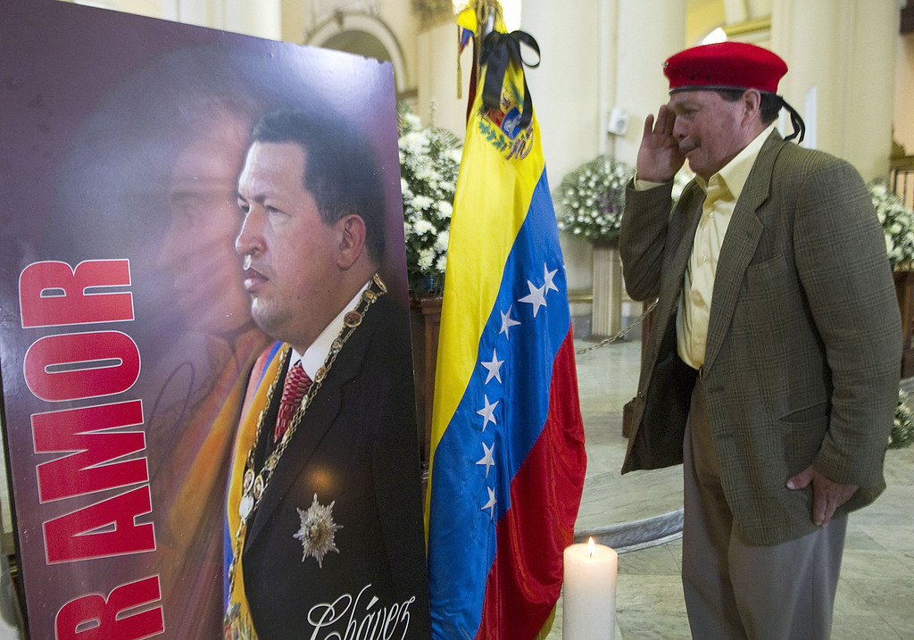 . A man salutes a poster with a picture of the late Venezuelan President Hugo Chavez at Primada Cathedral, on March 8, 2013, in Bogota, during a religious ceremony on behalf of his soul. AFP PHOTO / Raul  ARBOLEDA/AFP/Getty Images