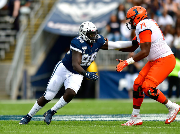 9/7/2019 Mike Orazzi | StaffrUConn's Lwal Uguak (98) and University of Illinois's Vederian Lowe (79) during Saturday's football game at Rentschler Field in East Hartford.