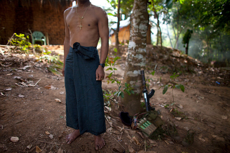 . A Kachin Independence Army (KIA) soldier wearing a cross stands watching after taking a bath at an outpost, a mile away from a hill top ceased by Myanmar\'s government troops, five miles away from the town of Laiza, in northern Myanmar\'s Kachin-controled region, Tuesday, Jan. 29, 2013. (AP Photo/Alexander F. Yuan)