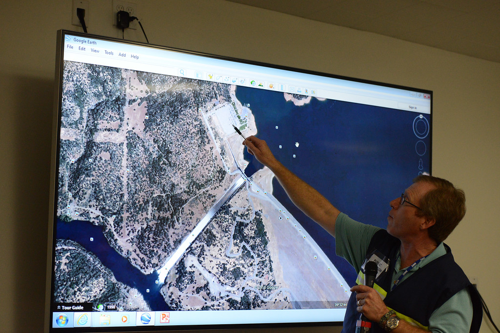 . California Department of Water Resources public information officer Eric See talks about water cresting the emergency spillway and flooding the Spillway Launch Ramp facility as water flows over the emergency spillway Saturday, Feb. 11, 2017, and in the main spillway in Oroville, California. (Dan Reidel -- Enterprise-Record)