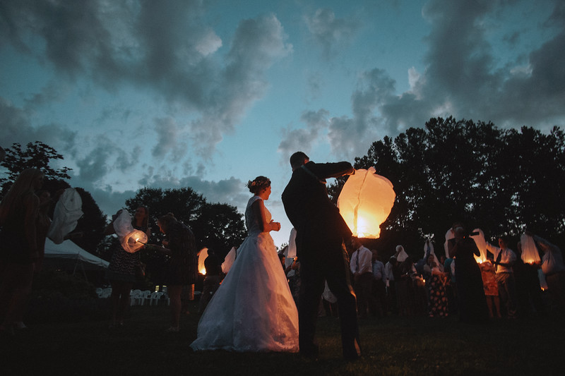 The groom lights a Chinese lantern as the bride watches the wedding guests light their lanterns.