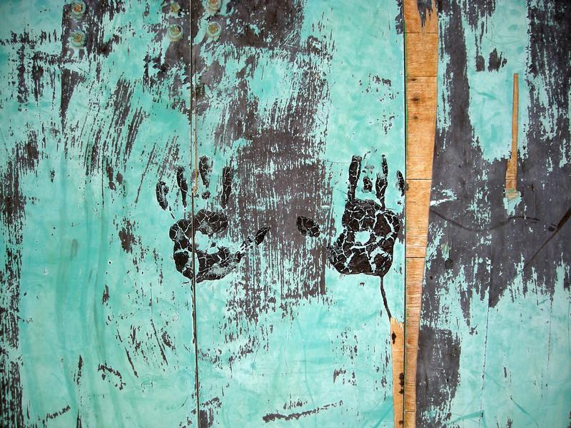 hand prints on wooded door