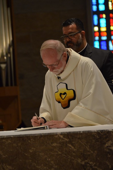 Fr. Ed signs the documents