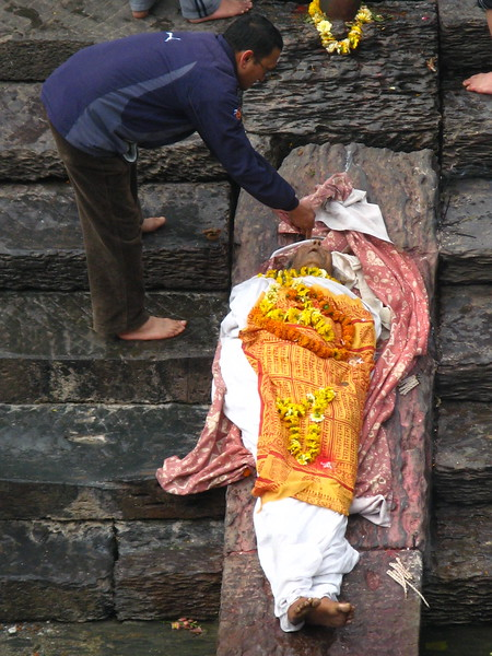 A family member performing rites on a Hindu body at Pashpupathinath Temple, Kathmandu