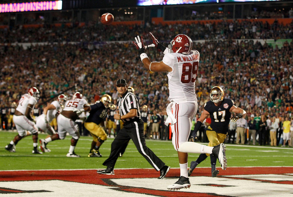 . Alabama Crimson Tide\'s Michael Williams (L) catches a touchdown pass next to Notre Dame Fighting Irish Zeke Motta (R) in the first quarter of their NCAA BCS National Championship college football game in Miami, Florida January 7, 2013. REUTERS/Jeff Haynes