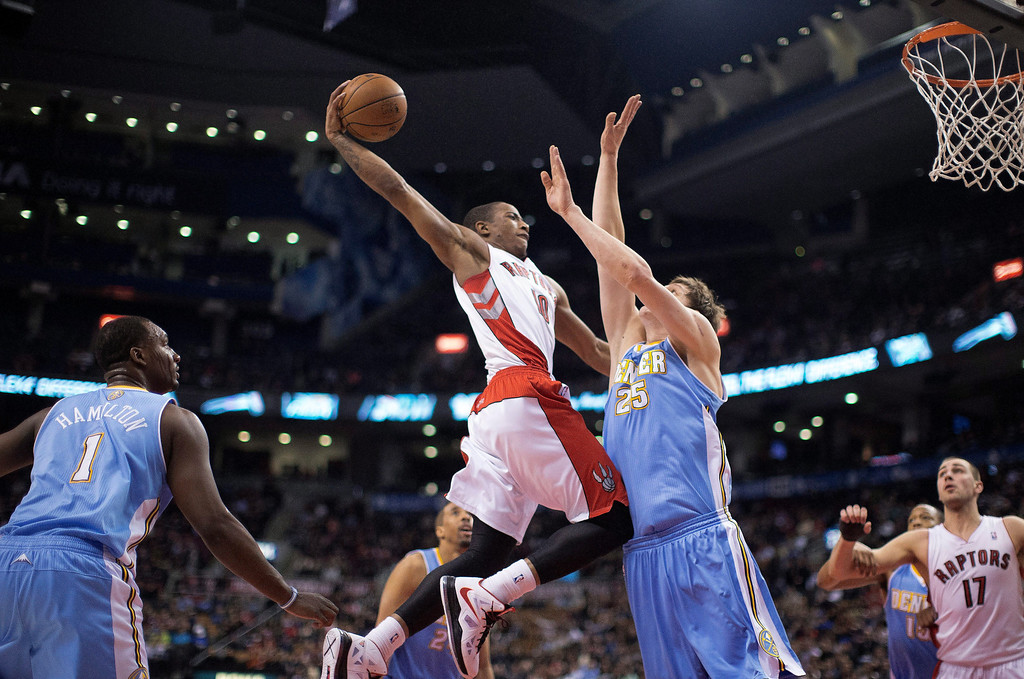 . Toronto Raptors\' DeMar DeRozan goes up for a dunk over Denver Nuggets\' Tomofey Mozgov during the first half of an NBA basketball game in Toronto on Tuesday, Feb. 12, 2013. (AP Photo/The Canadian Press, Chris Young)