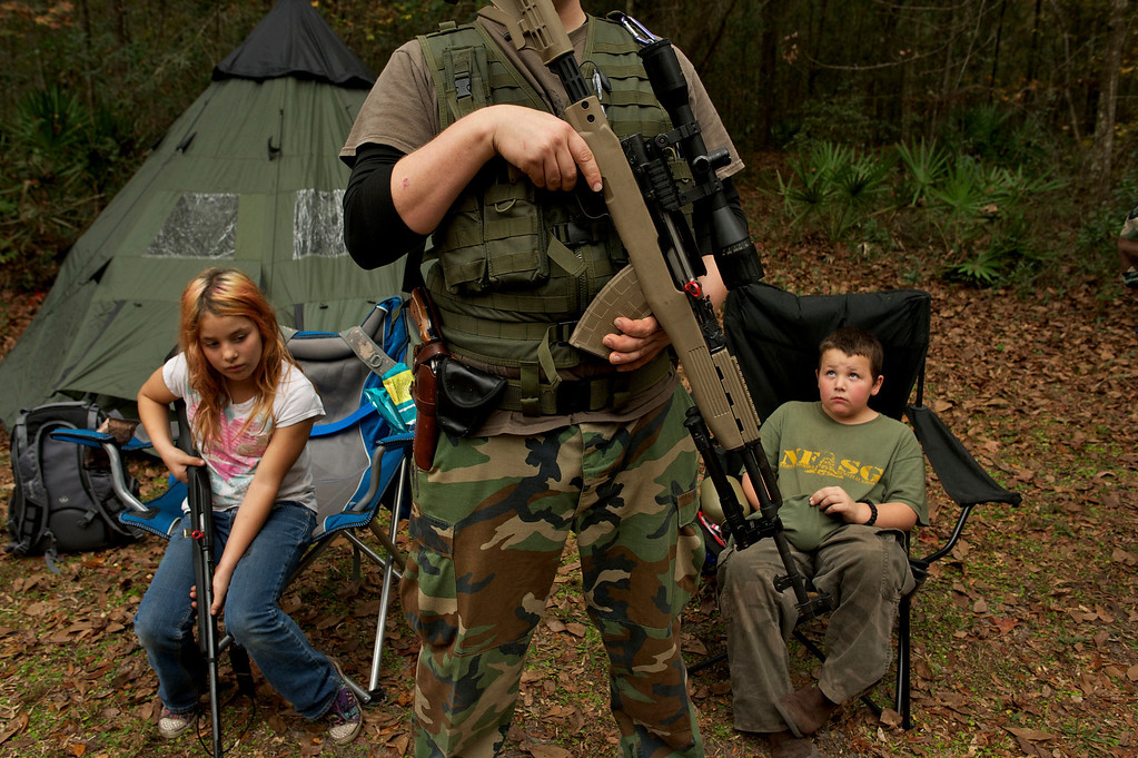 ". Members of the North Florida Survival Group wait with their rifles before heading out to perform enemy contact drills during a field training exercise in Old Town, Florida, December 8, 2012. The group trains children and adults alike to handle weapons and survive in the wild. The group passionately supports the right of U.S. citizens to bear arms and its website states that it aims to teach ""patriots to survive in order to protect and defend our Constitution against all enemy threats\"".   REUTERS/Brian Blanco"