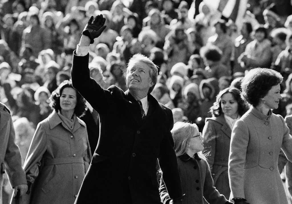 . President Jimmy Carter waves to the crowd while walking with his wife Rosalynn along Pennsylvania Avenue and their daughter Amy.  The Carters elected to walk the parade route from the Capitol to the White House following his inauguration in Washington, on Thursday, Jan. 20, 1977. (AP Photo/Suzanne Vlamis)
