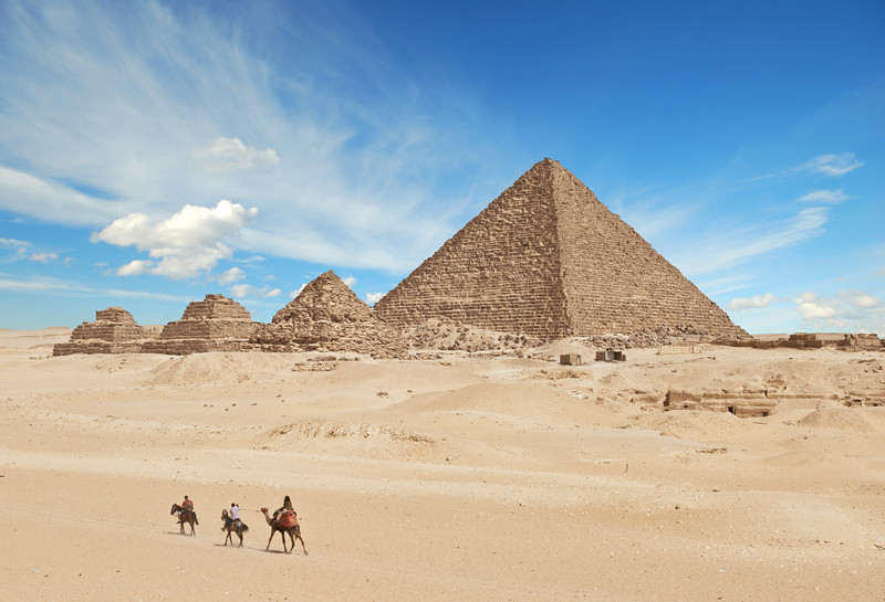Four pyramids surrounded by desert and a blue sky.