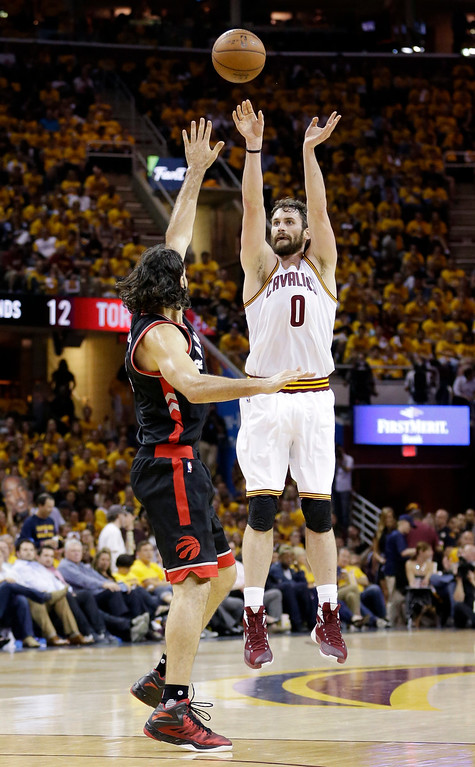 . Cleveland Cavaliers\' Kevin Love shoots over Toronto Raptors\' Luis Scola during the second half of Game 5 of the Eastern Conference finals on May 25 in Cleveland. Love led the Cavs in points with 25, in the team\'s 116-78 victory. Cleveland leads the series, 3-2. (AP Photo/Tony Dejak)