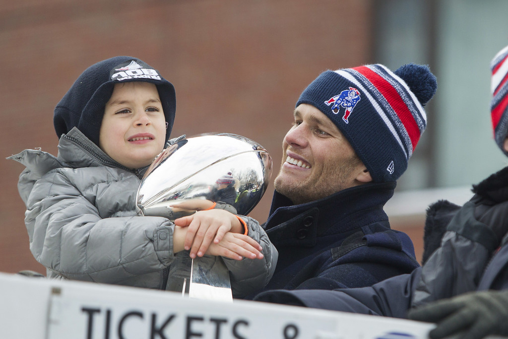 . Benjamin Brady (L) holds the Lombardi trophy next to his dad, Patriots quarterback Tom Brady, on a duck boat during the New England Patriots victory parade on February 4, 2015 in Boston, Massachusetts. (Photo by Scott Eisen/Getty Images)