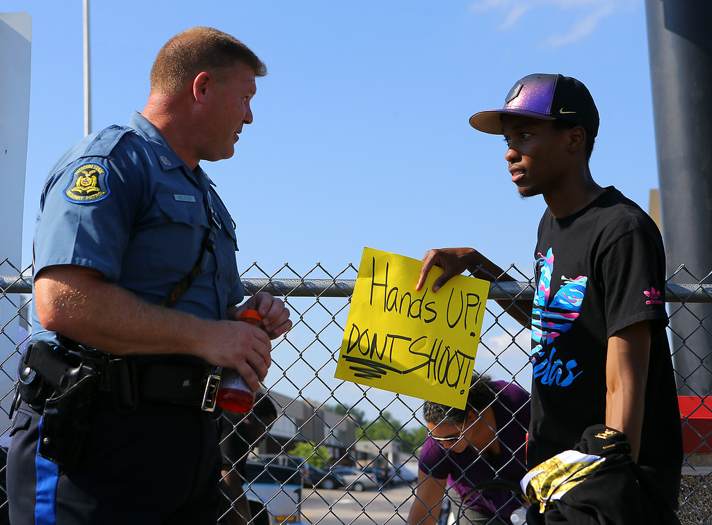". In an effort to foster some good will Missouri State Higway Patrol trooper D. Reuter chats with protester Robert Clark along West Florissant Avenue on Tuesday, Aug. 19, 2014, in Ferguson, Mo.   The city of Ferguson, Missouri, says it working hard to better connect with the community and learn from the ""discord and heartbreak\"" that followed the shooting death of 18-year-old Michael Brown by a police officer.  (AP Photo/Atlanta Journal-Constitution, Curtis Compton)"