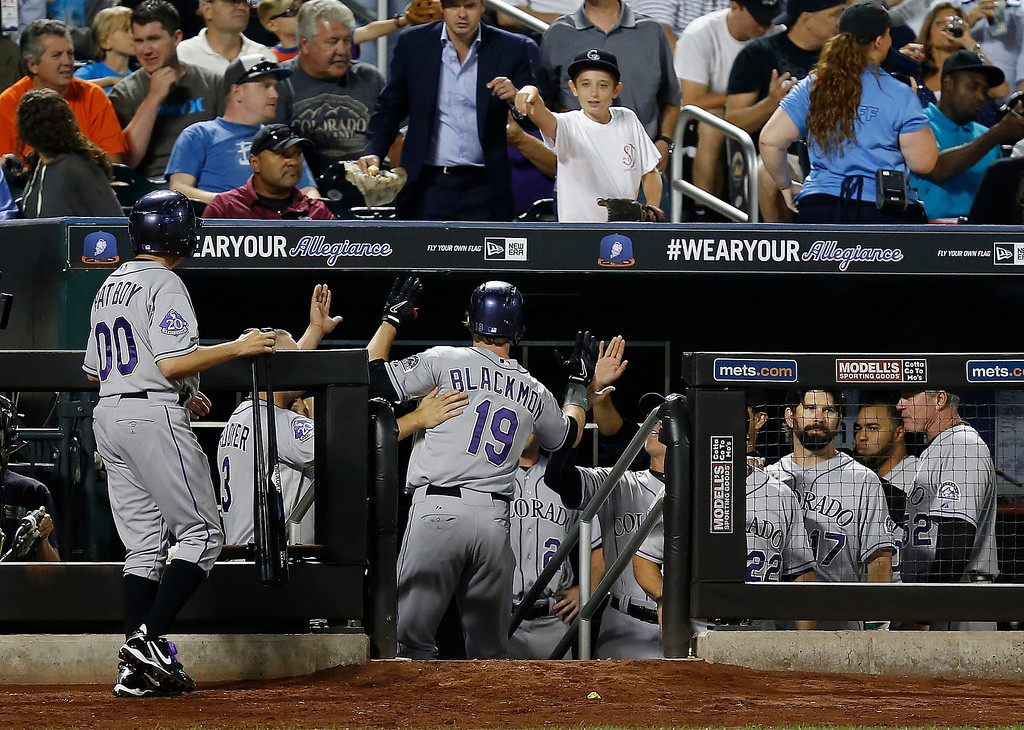 . Colorado Rockies\' Charlie Blackmon (19) celebrates with his teammates after hitting a solo home run in the sixth inning of a baseball game against the New York Mets at Citi Field, Tuesday, Aug. 6, 2013, in New York. (AP Photo/John Minchillo)