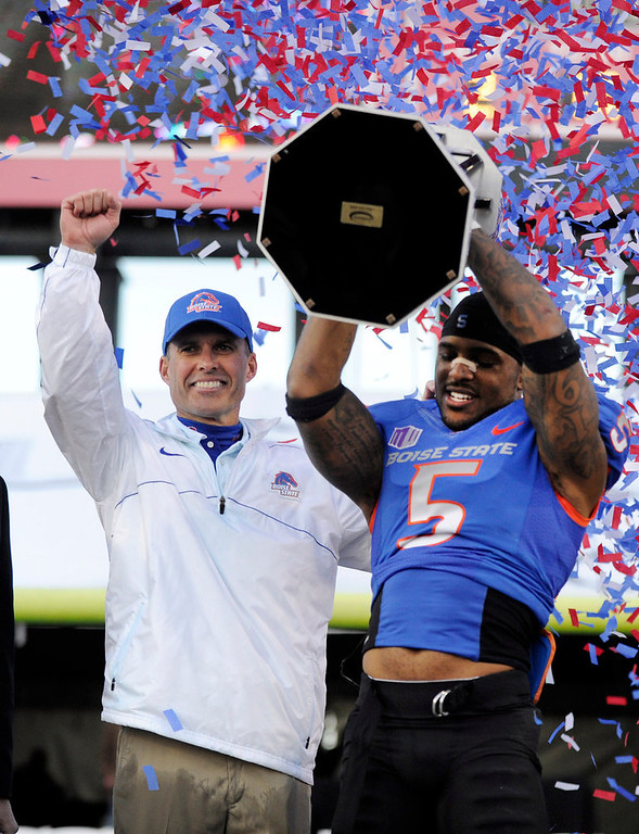 . Boise State coach Chris Peterson, left, gestures as cornerback Jamar Taylor holds the championship trophy after the MAACO Bowl NCAA college football game against Washington, Saturday, Dec. 22, 2012, in Las Vegas. Boise State defeated Washington 28-26. (AP Photo/David Becker)