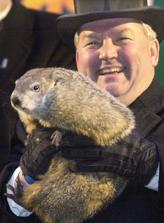 . ** CORRECTS NAME OF HANDLER TO BILL DEELEY, NOT BILL FEELEY IN AP PHOTOS KBS101 AND KBS102 TRANSMITTED FEB. 2, 2003 ** The weather predicting groundhog, Punxsutawney Phil, is raised by handler Bill Deeley, right, Sunday, Feb. 2, 2003 in Punxsutawney, Pa., after Groundhog Club President Bill Cooper said Phil saw his shadow and winter will continue for six more weeks.  (AP Photo/Keith Srakocic)
