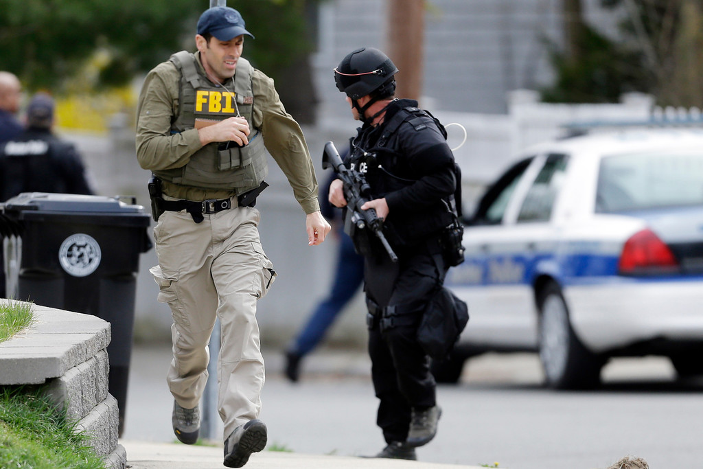. A police officer and a Federal Bureau of Investigation agent run as they conduct a search for a suspect in the Boston Marathon bombings, Friday, April 19, 2013, in Watertown, Mass.  (AP Photo/Matt Rourke)